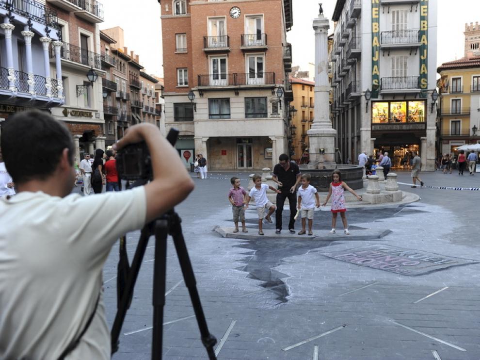 Un grupo de personas juega sobre la pasarela que salva la grieta simulada en la plaza del Torico.