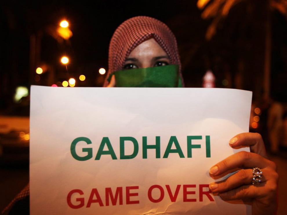 Opositora a Gadafi muestra un cartel en su contra
