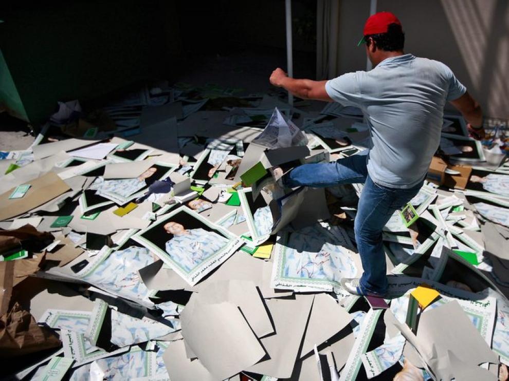 Un disidente destruye unos carteles del líder libio