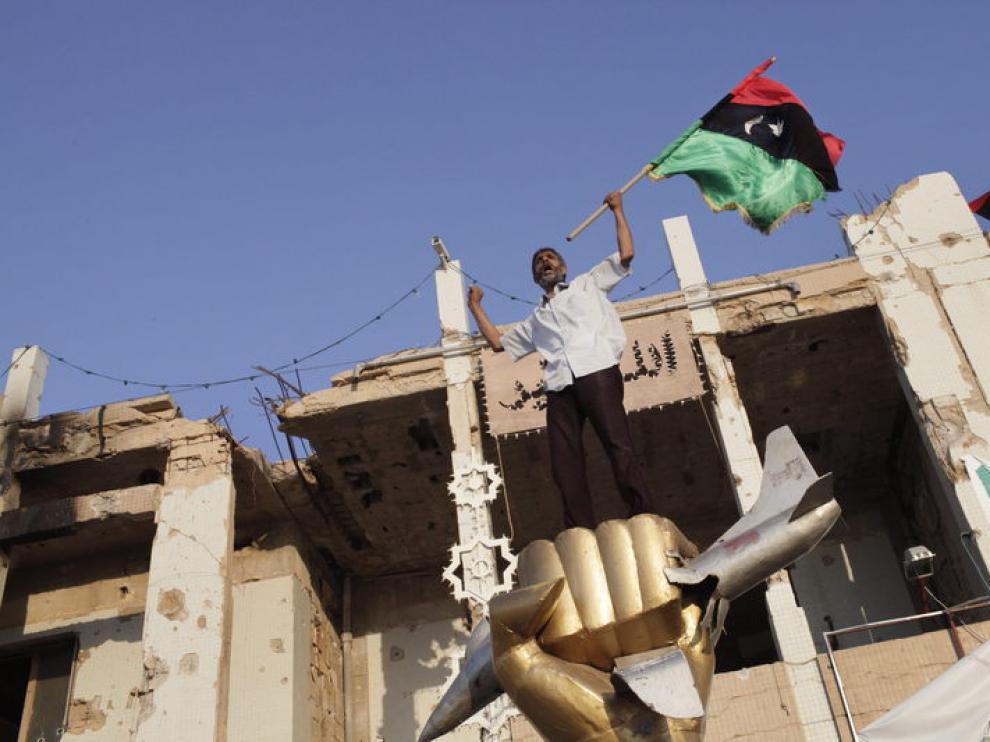 Un rebelde libio ondea su bandera sobre el monumento símbolo del dictador libio