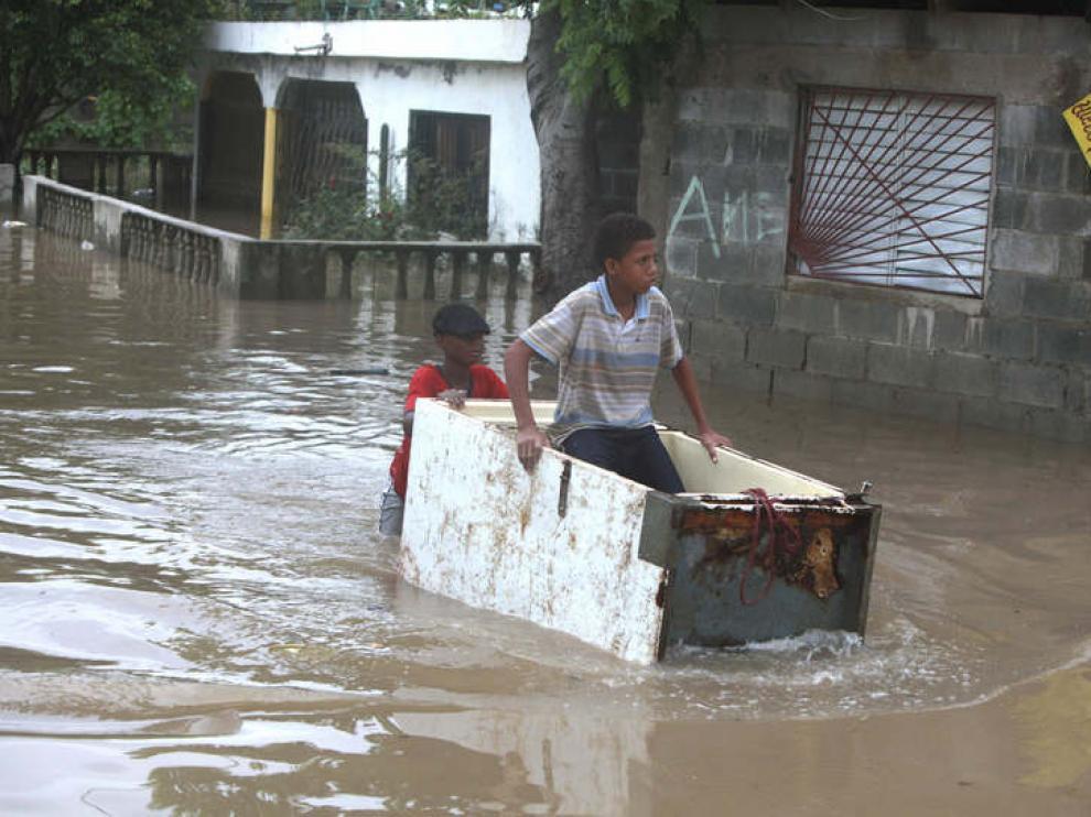 Un joven transportando a otro en medio de una calle inundada