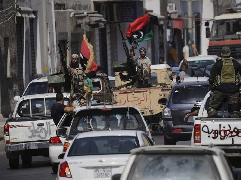 Unos soldados rebeldes libios escoltan a miembros del Consejo de Transición