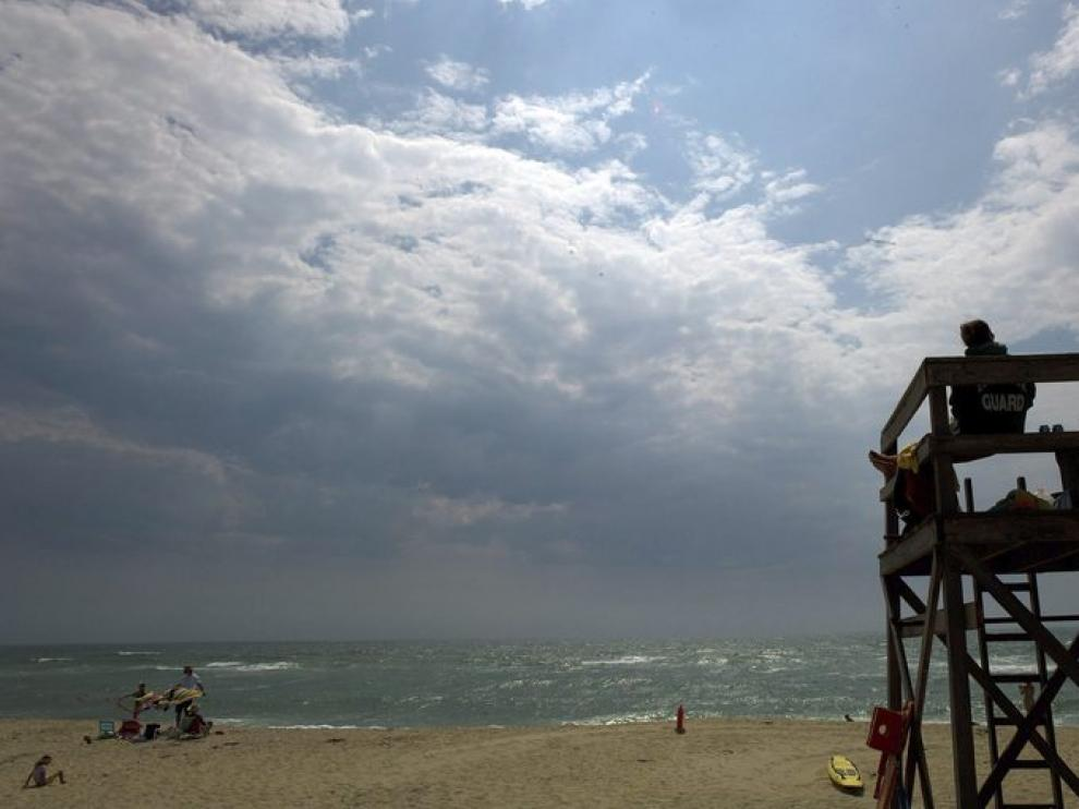 Un socorrista observa el cielo ante la llegada de Irene.