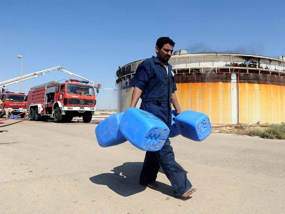 Un hombre carga botes vacíos junto a un tanque de petróleo en Brega