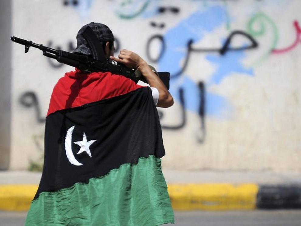 Un rebelde se cubre con una bandera de Libia