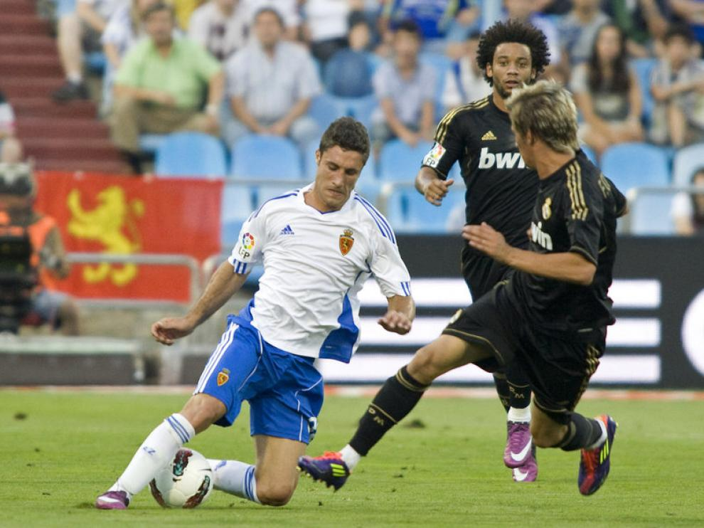 Zucilini trata de zafarse de dos defensas del Madrid.