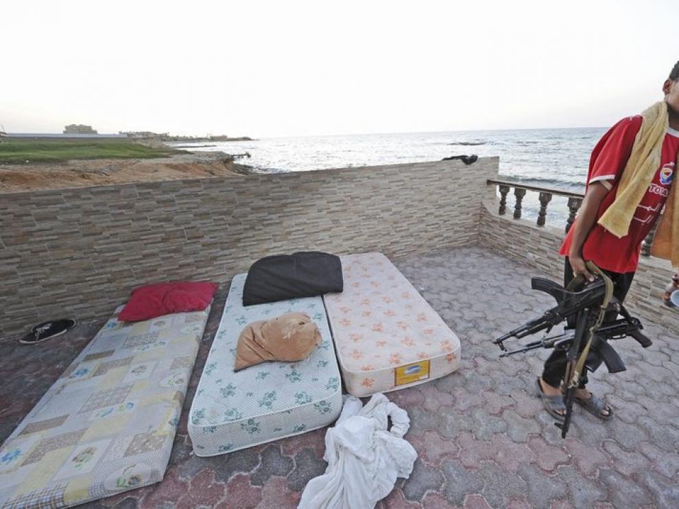 Un rebelde libio, fusil en mano, inspecciona la casa de Saif al-Islam, hijo del líder libio, Muamar al-Gadafi, en Trípoli