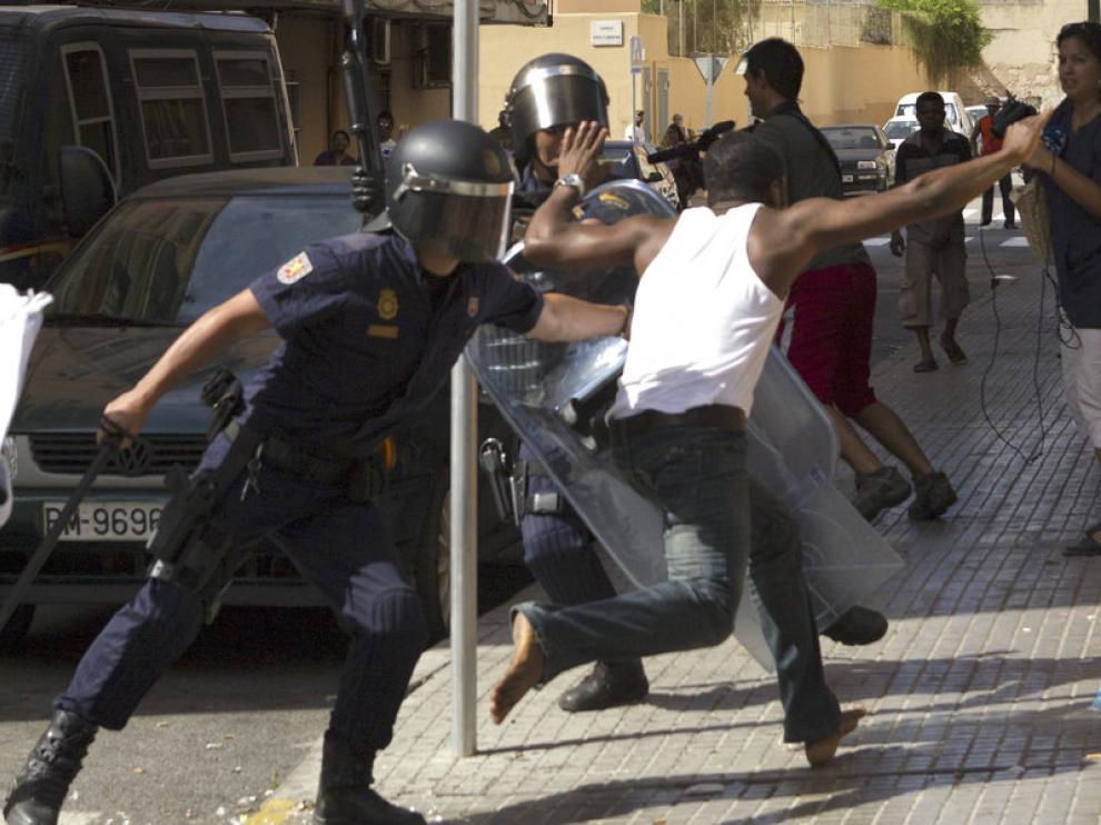 Los antidisturbios intentan detener a un ciudadano nigeriano.