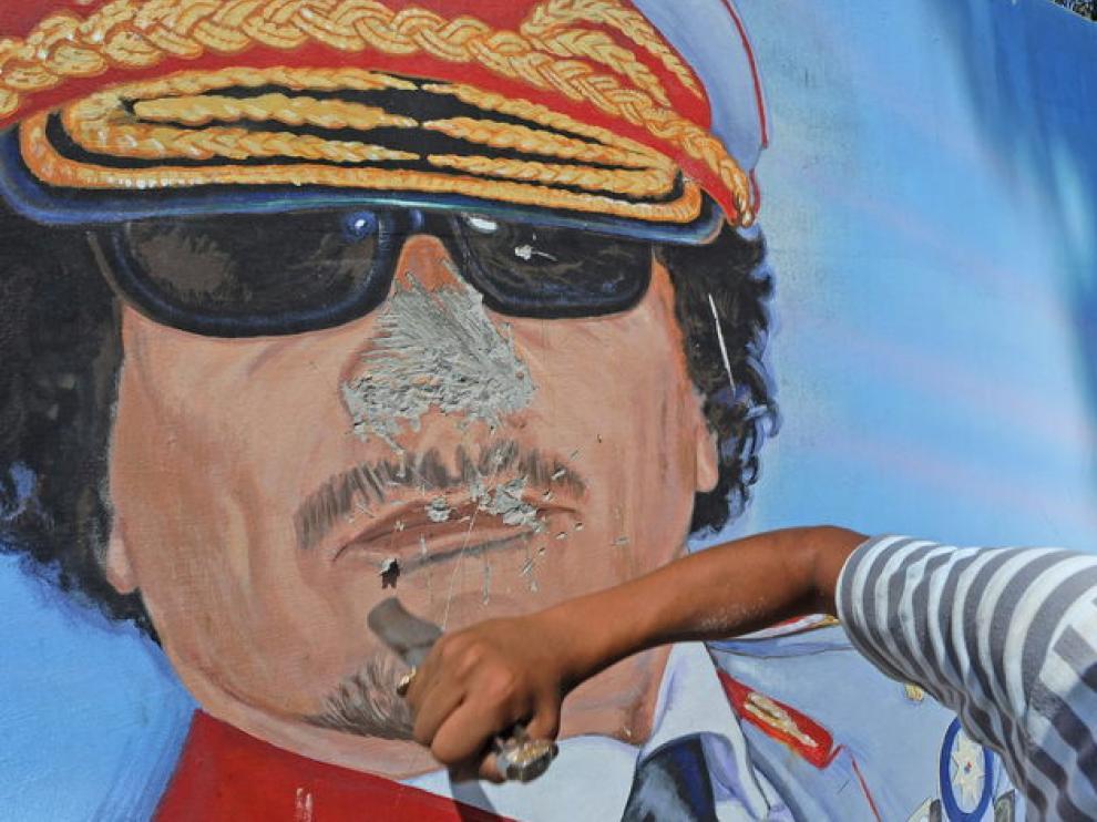 Un hombre destroza un mural de Gadafi