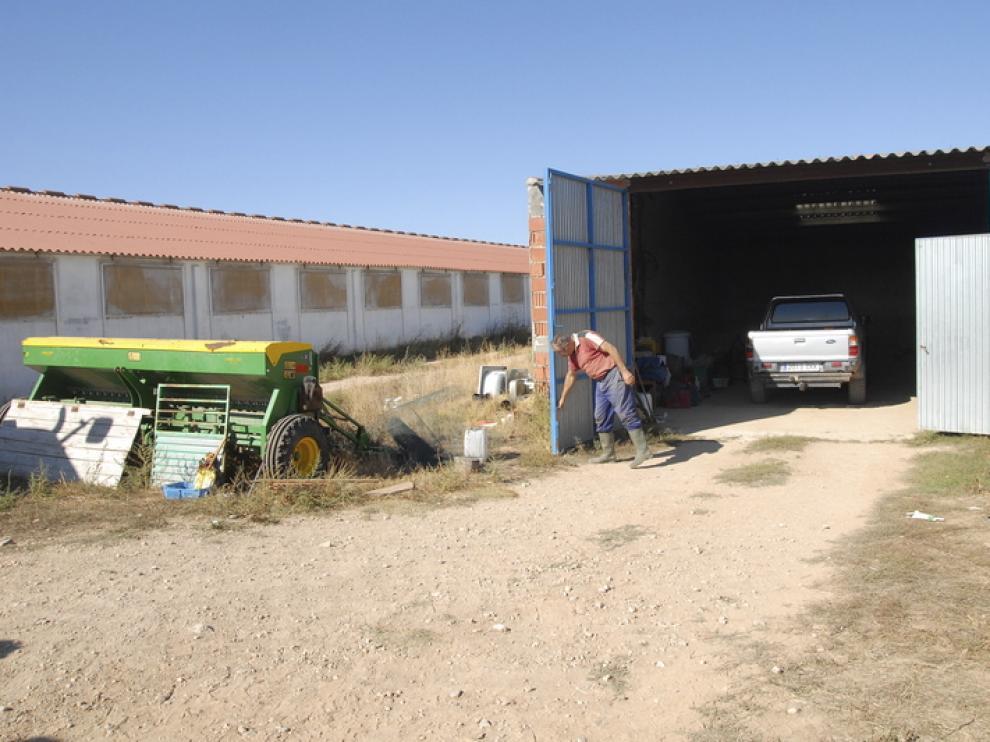 El propietario de un tractor robado abre las puertas de la cochera de donde fue sustraído.