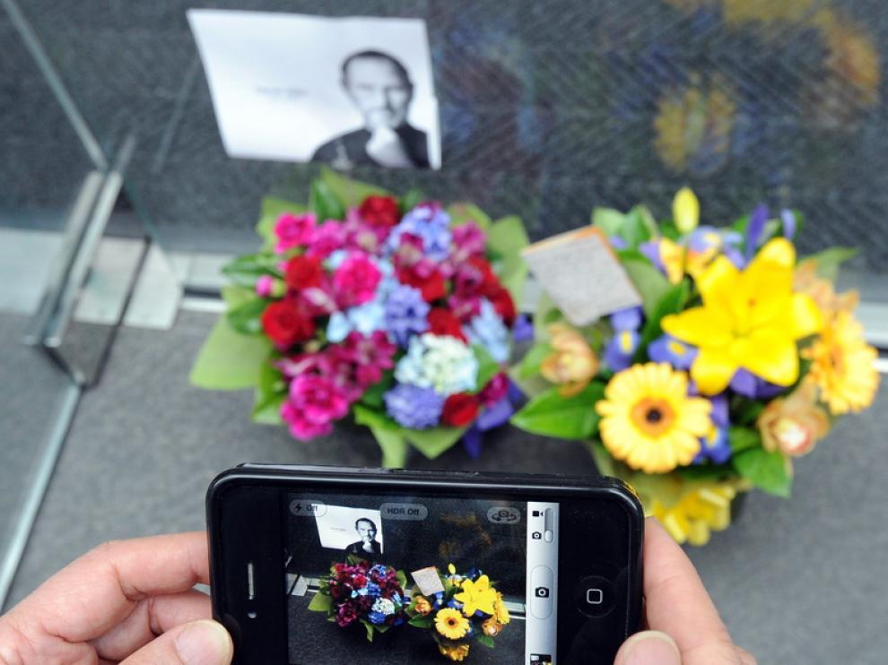 Un ciudadano toma una foto de un altar improvisado con su iPhone4