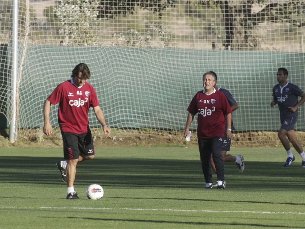 Gilvan hace carrera continua mientras el míster, Quique Hernández, da indicaciones a otros futbolistas.