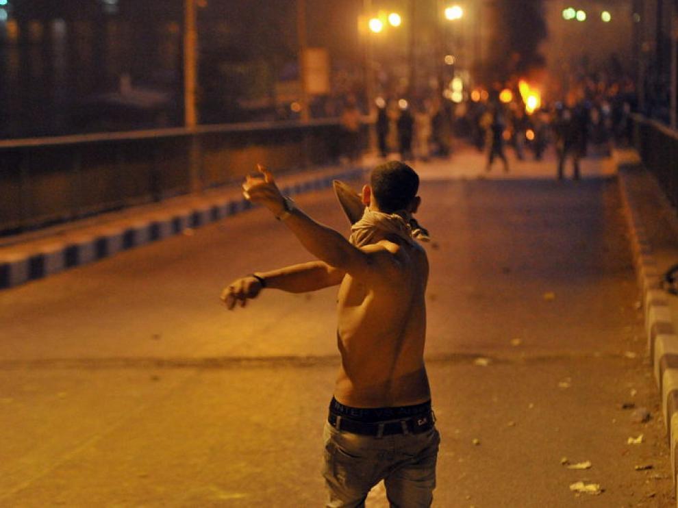 .- Un joven egipcio enfrenta a fuerzas de seguridad egipcias durante una protesta llevada a cabo frente al edificio de la radiotelevisión en El Cairo