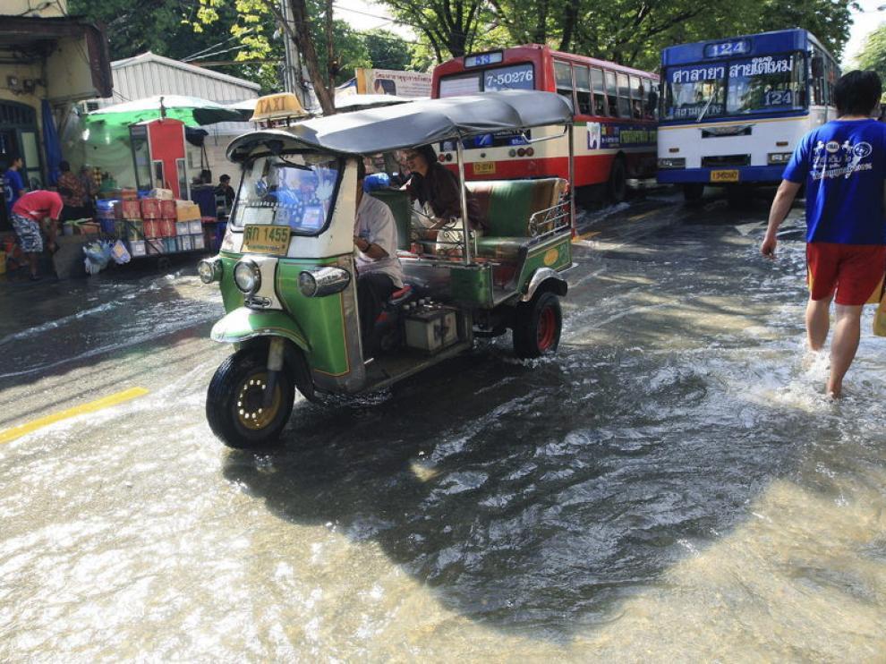Un tuk tuk circula por las calles inundadas de Bangkok