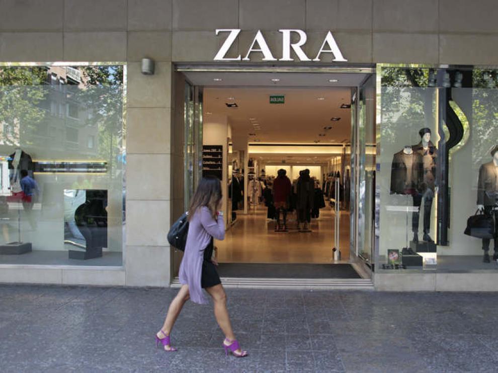Una joven pasea frente a un escaparate.