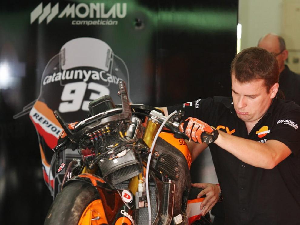 Un mecánico mueve la moto accidentada del piloto español Marc Marquez
