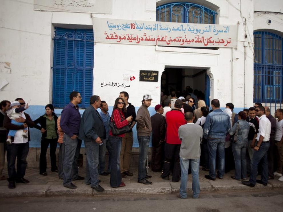 Decenas de personas esperan para votar en un colegio electoral