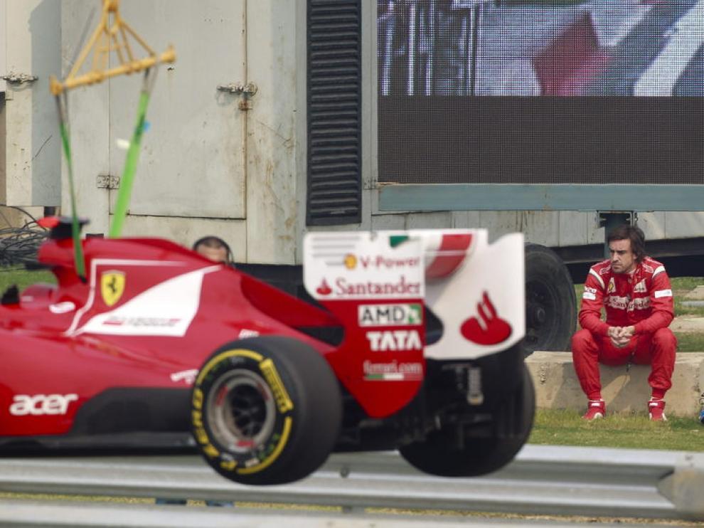 - El piloto español Fernando Alonso, de la escudería Ferrari, observa sentado fuera de pista cómo una grúa retira su monoplaza