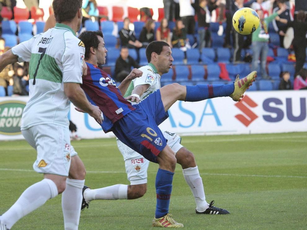 Camacho trata de controlar el balón ante dos defensores del Elche