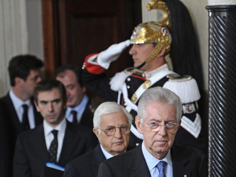 El excomisario europeo y senador italiano, Mario Monti (dcha), sale de la rueda de prensa ofrecida para presentar la lista de ministros tras aceptar el cargo de presidente del Gobierno de Italia
