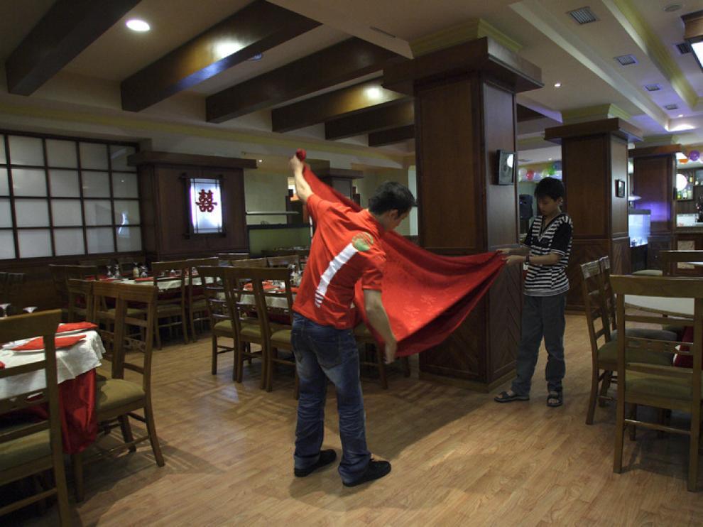 Unos empresarios de nacionalidad china trabajan en su local hostelero