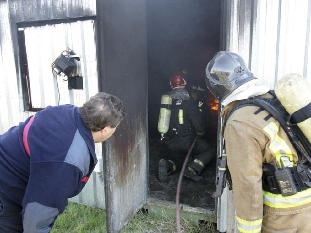 Unos bomberos observan desde el exterior de las instalaciones la actuación de sus compañeros.