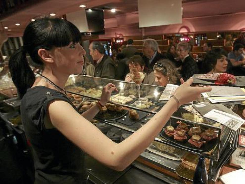 Una camarera sirve una tapa ante un público muy numeroso