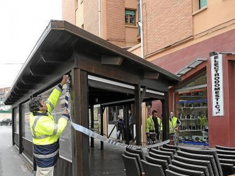 Operarios municipales desmantelan la terraza.