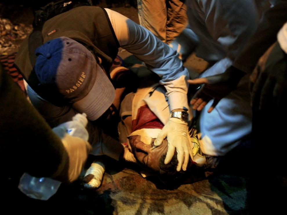 Los médicos atienden a un herido durante los enfrentamientos acontecidos en la plaza de Tahrir.