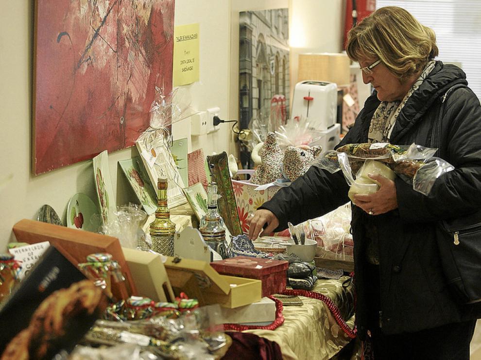 Una mujer selecciona algunos productos de alimentación del mercadillo de la AECC.