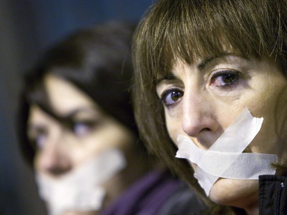 Dos mujeres se tapan la boca durante una manifestación contra la violencia de género en Zaragoza
