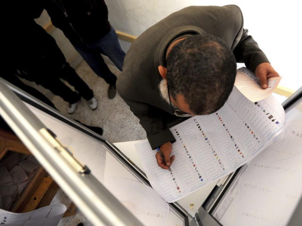 Un hombre cumplimenta su papeleta antes de ejercer su derecho al voto en El Cairo