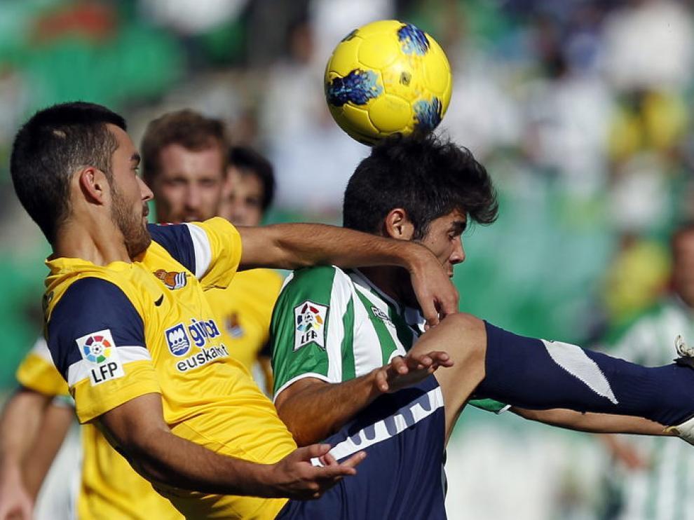 El jugador del Real Betis Pozuelo (d), y Estrada (i), de la Real Sociedad
