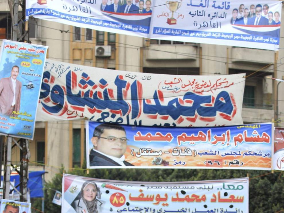 Dos mujeres y un niño pasean ante carteles electorales en El Cairo