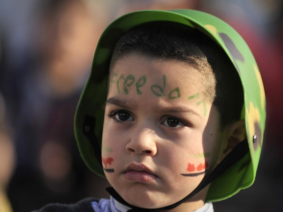 Un niño sirio con la palabra libertad pintada en la cara