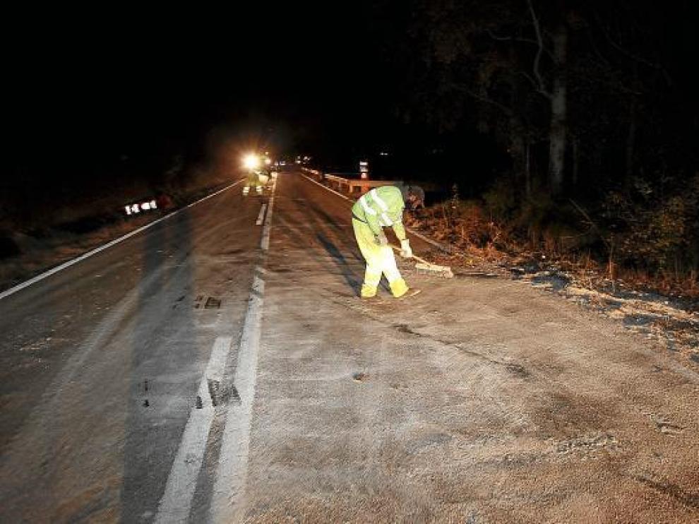 Operarios de Fomento retiran la arena vertida sobre la N-330 por el camión accidentado.
