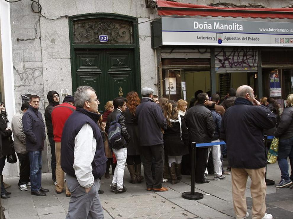 Decenas de personas esperan su turno ante una administración de lotería en Madrid