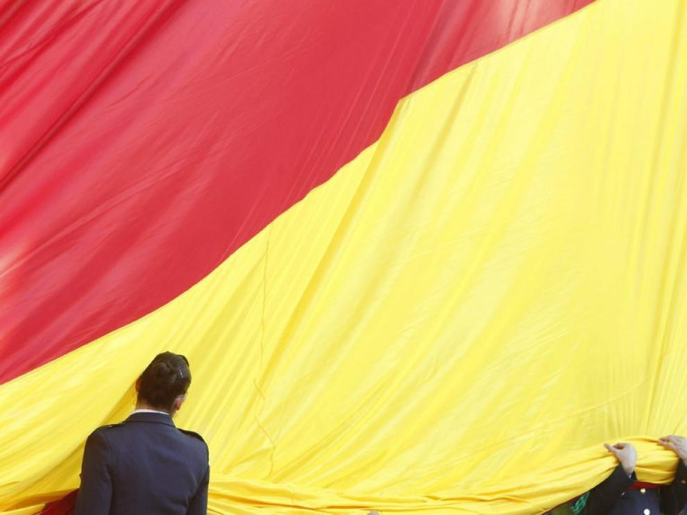 Dos militares despliegan la bandera nacional durante el acto solemne de izado de la enseña en Madrid