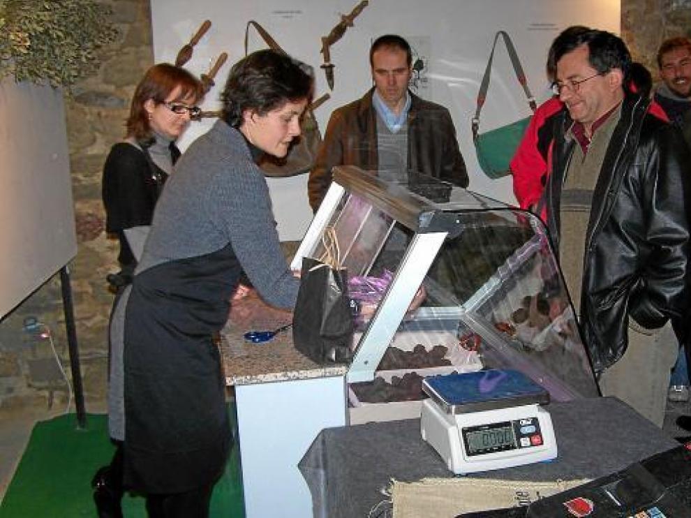 Varios turistas (el pasado invierno) se interesan por la trufa que oferta el mercado de Graus.