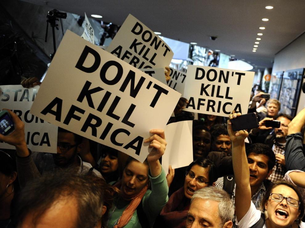 Una multitud se manifiesta frente al salón plenario en contra del cambio climático.