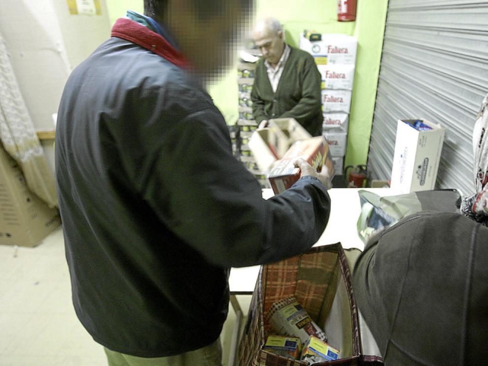 Mohamed y su mujer recogen el lote de alimentos en el centro de la calle de San Lorenzo.