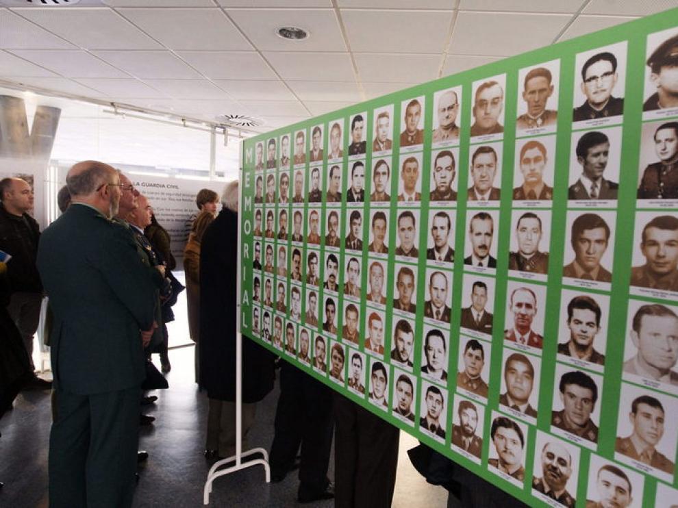 Un miembro de la Benemérita contempla un panel con las fotografías de víctimas del terrorismo