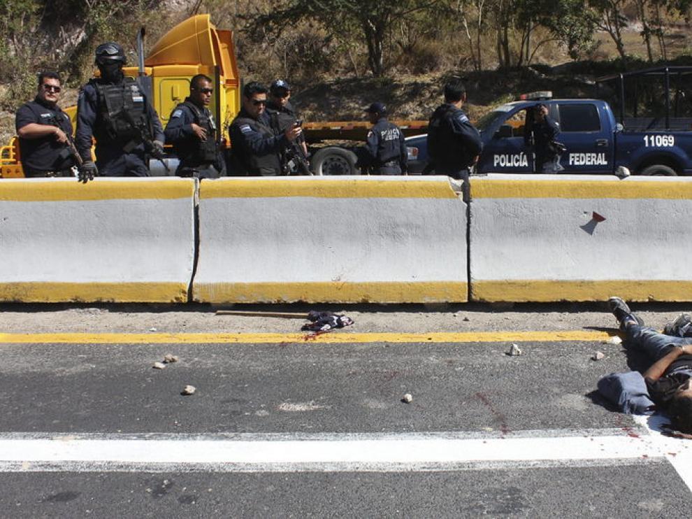 Agentes federales observan el cuerpo de uno de los dos muertos que resultaron de un enfrentamiento entre estudiantes y policías