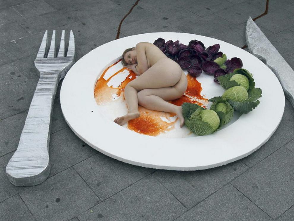 La organización AnimaNaturalis ha realizado hoy en Barcelona una performance con un plato gigante que simula ser carne humana
