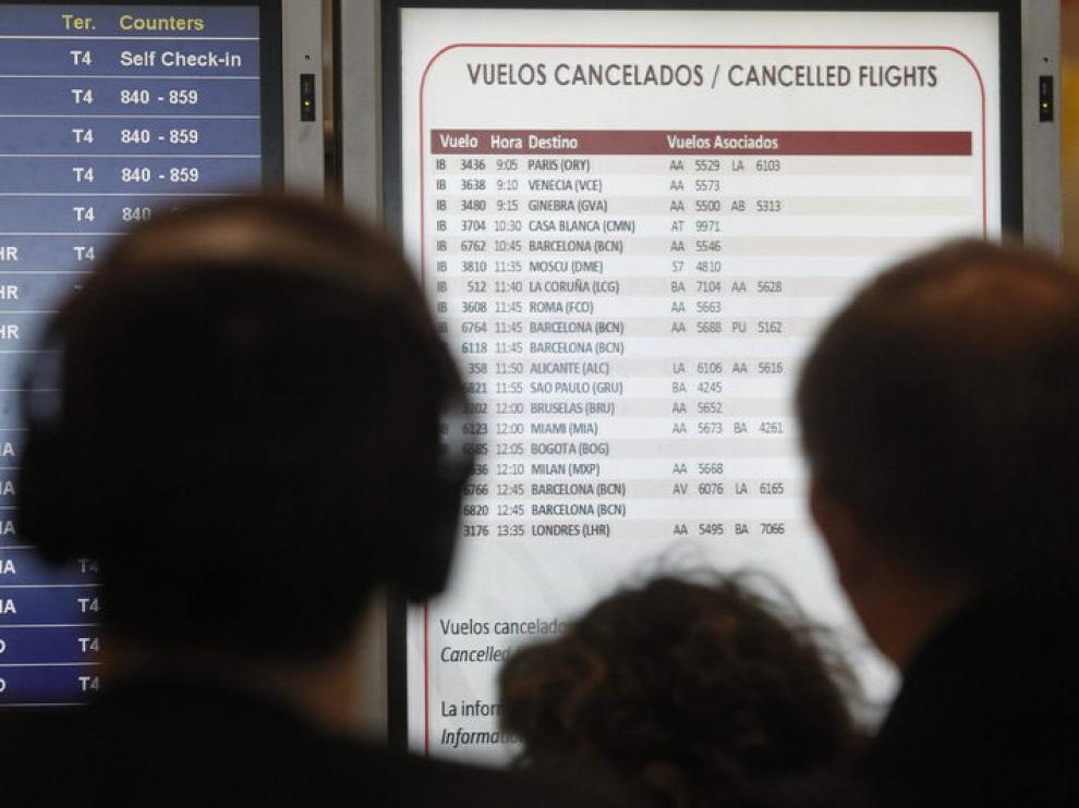 Pasajeros afectados por la huelga de pilotos de Iberia observan en la T-4