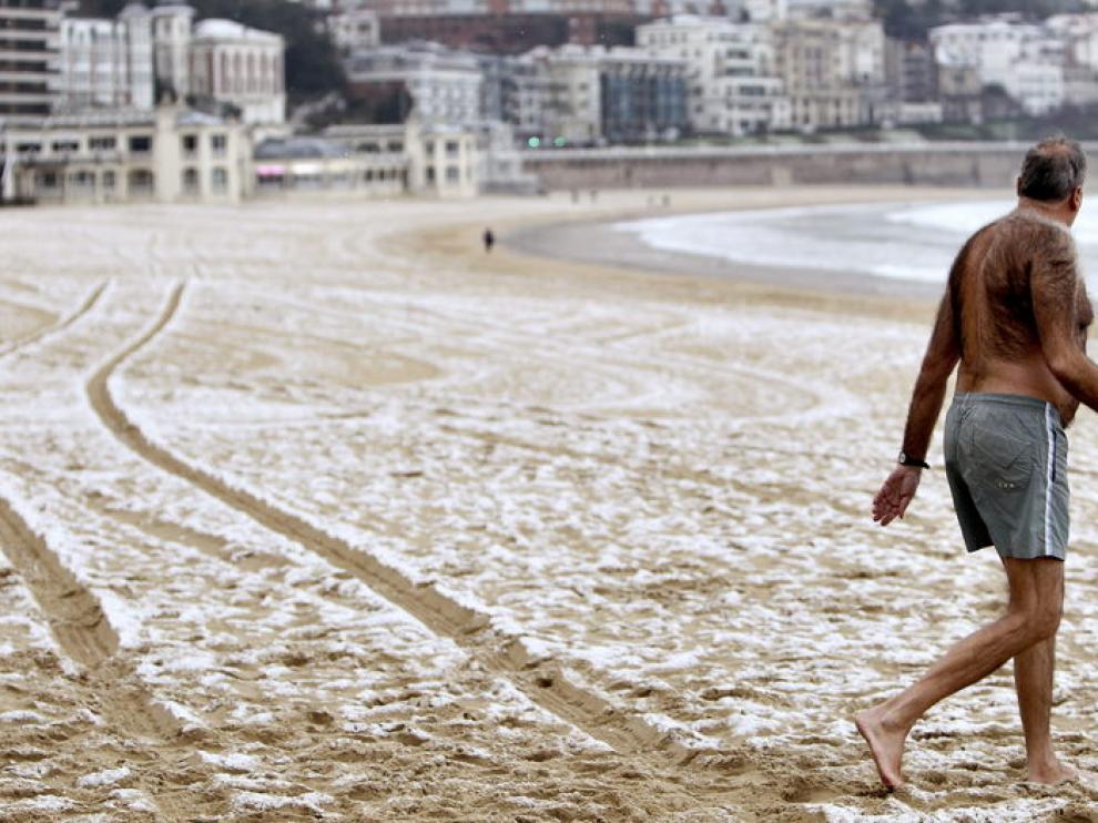 Un hombre se mete al agua en la playa de la Concha de San Sebastián