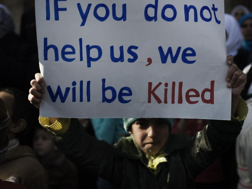 Un niño sirio enarbola un cartel pidiendo ayuda