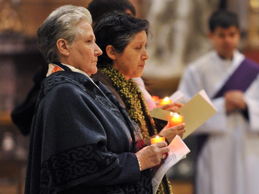 Marie Callins (i) sostiene una vela durante el acto.