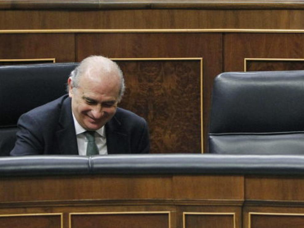 El ministro del Interior (i) y el de Justicia (d) sonríen en sus escaños durante el Pleno.