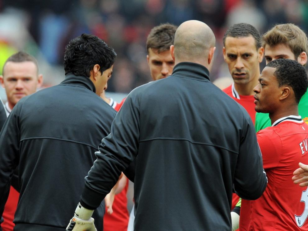 Evra tiende su mano al paso de Suárez